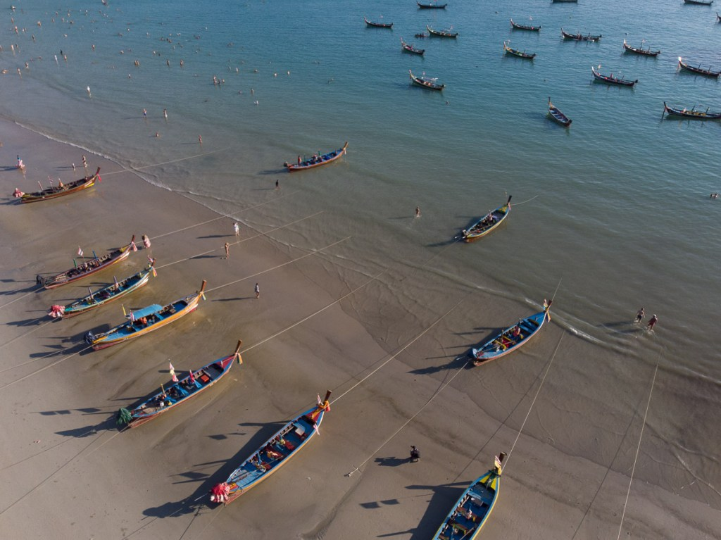 Low tide at Kata beach with longtail boats a shore