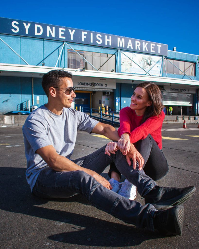 couple sat in on the floor outside market