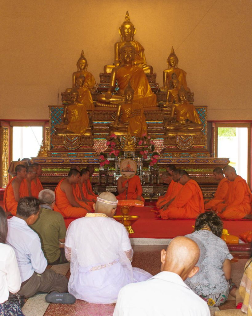 Monks in orange robes pray with the public under golden buddha statues