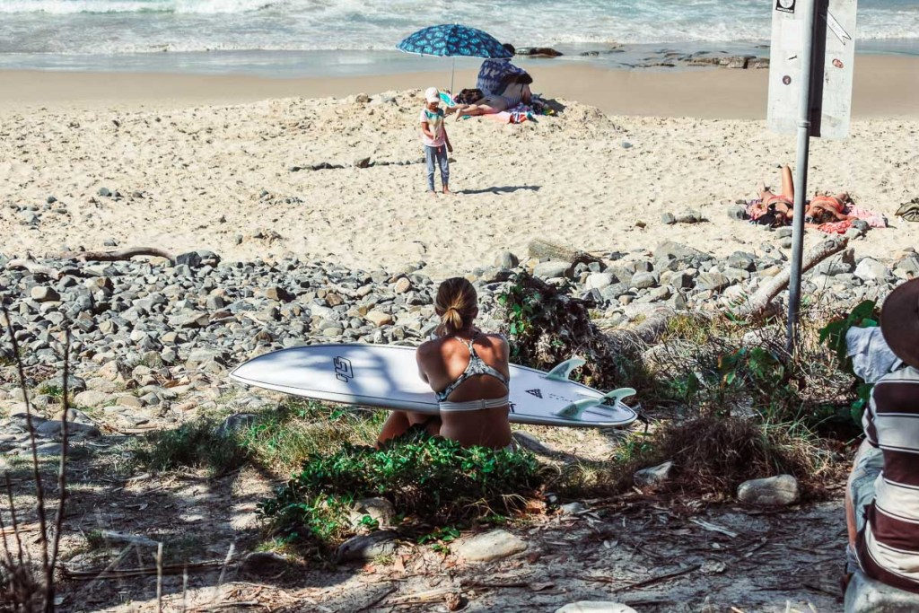 People with surf boards at tea tree bay beach