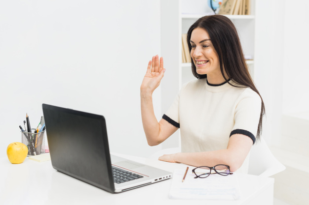 woman waving at the laptop