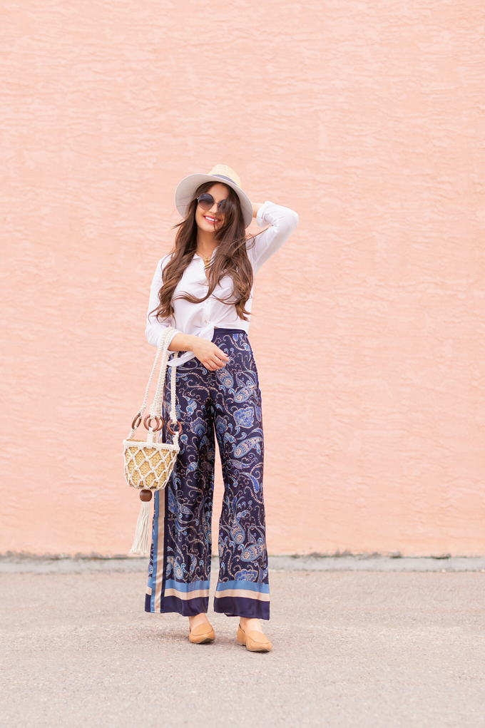 Out of Office | Brunette woman wearing paisley palazzo pants, a white linen shirt, a straw fedora, a macrame bucket bag, leather pointed toe flats and round sunglasses | Canadian May Long Weekend Outfit Ideas | Roadtrip Outfit Ideas | Calgary Fashion & Lifestyle Blogger // JustineCelina.com