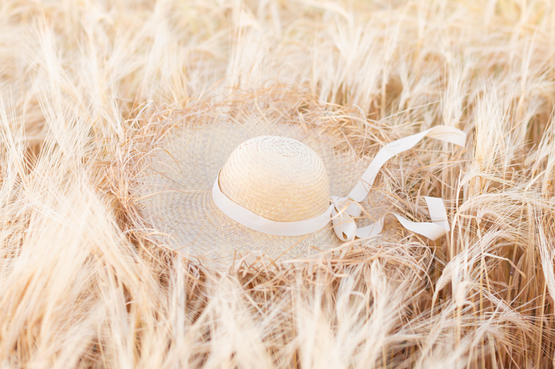 Summer 2020 Lookbook | Boho Summer 2020 Outfit Ideas | Summer Capsule Wardrobe | Summer Quarantine Outfits | Classic Summer Outfit Ideas | The Best Linen Dresses 2020 | Sunset Photoshoot | Summer to Fall Outfit Ideas | Classic Affordable Summer Style | Summer 2020 Trends | Oversized Fringed Brim Straw Hat with a Cream Ribbon resting on the tops of Sunlit Barley Field during Golden Hour | The Best Frayed Brim Straw Hats | Calgary Alberta Fashion & Lifestyle Blogger // JustineCelina.com