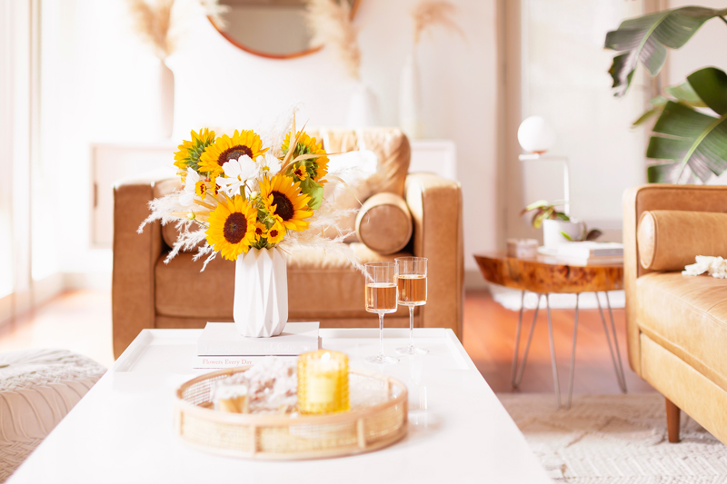 Our Transitional Summer Meets Autumn Decor | Summer to Fall Decor | September Decorations | Sunflower Decor | Easy Fall Decorating Ideas 2020 | Affordable Fall Decor | Simple Fall Decor Ideas | Fall Apartment Decor JustineCelina's Inner City Calgary bohemian, mid-century modern Living Room | Cheerful Sunflower Arrangement with white Cosmos and Pampas Grass on a coffee table with 2 glasses of rosé | Summer Meets Autumn Decor | Sunflower Decor Ideas | Calgary Lifestyle Blogger // JustineCelina.com