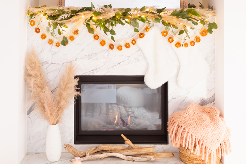 Mid Century Meets Boho Holiday Decor | Bright airy Mid Century Modern Living Room with a boho eucalyptus garland with pampas grass, fresh cedar, bleached Italian ruscus and a beaded dried orange garland | Boho Christmas Decorating Ideas for Apartments | Boho Holiday Fireplace Decor | DIY Orange Slice Garland | Bohemian Holiday Home Tour 2020 | Boho Chic Christmas Decor | Glam neutral holiday decor | Warm toned Holiday decor | Fun Holiday Decor | Dried Fruit Holiday Decor // JustineCelina.com