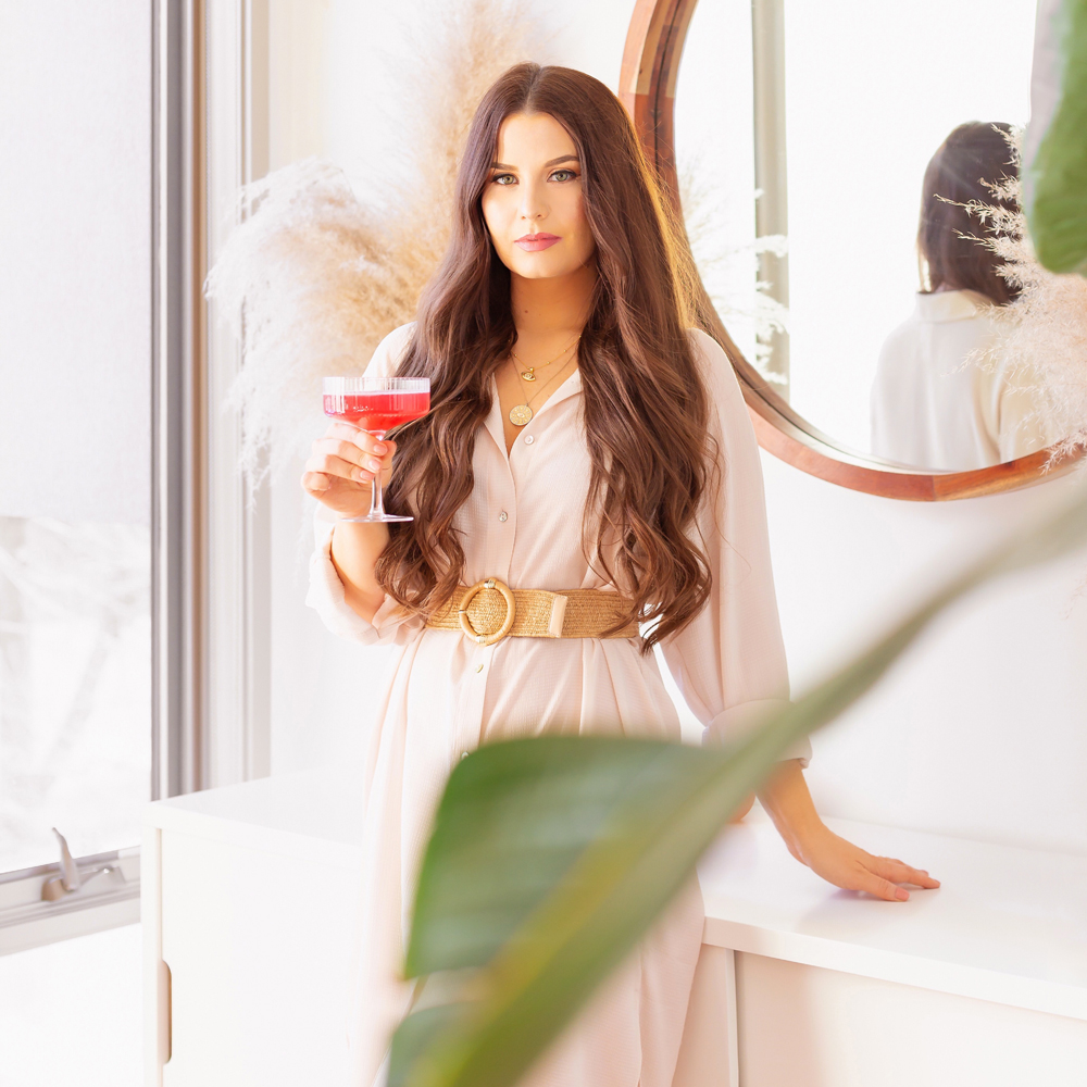 My Dry January Experience | Smiling brunette woman holding a champagne flute full of watermelon kombucha in a bright and airy living room | Calgary Lifestyle Blogger // JustineCelina.com