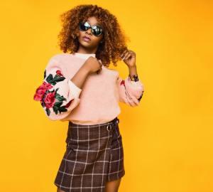 Stoere vrouw met roze trui en rokje aan, zonnebril