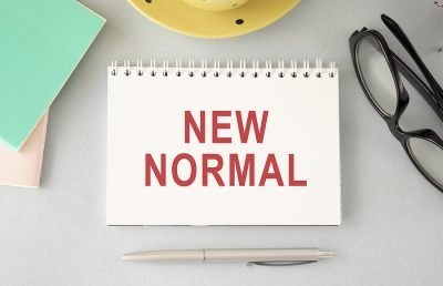 The concept of a new normal, where a situation requires a change to our lifestyle. Presented as a word written in notebook on office desk.
