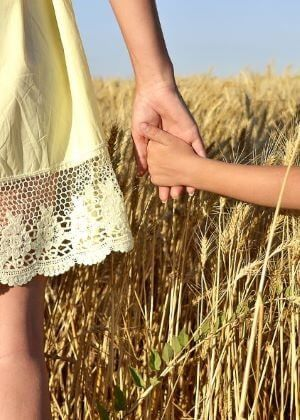 mother in yellow summer dress holding hand of child and walking through wheat field