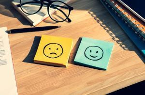 Happy and sad faces drawn on sticky notes, representing the concept of human emotions.