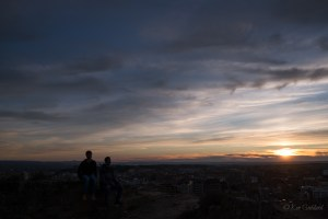 Two men silhouetted above a city at sunset