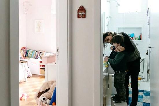 """Mãe ajudando seu filho a escovar os dentes - Imagem de Mika Amanto, do projeto """"A day in the life of..."""", que mostra cotidianos de famílias pelo mundo."""