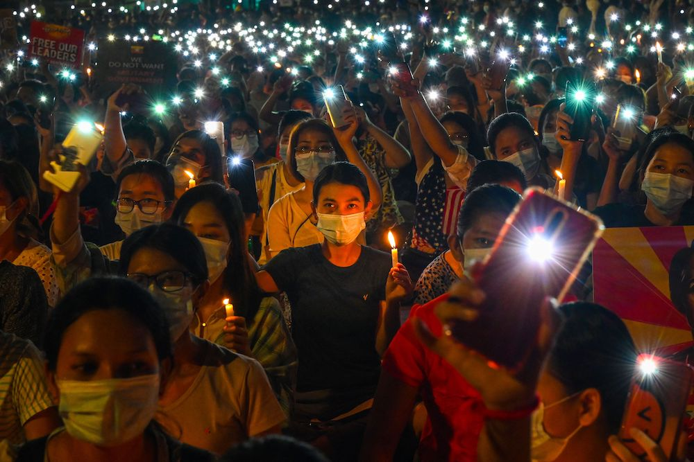 Protesters hold up their mobile phones and candles during a candlelight vigil to honor those who have died during demonstrations against the military coup in Yangon on March 13, 2021. They wear face masks to protect against COVID-19.