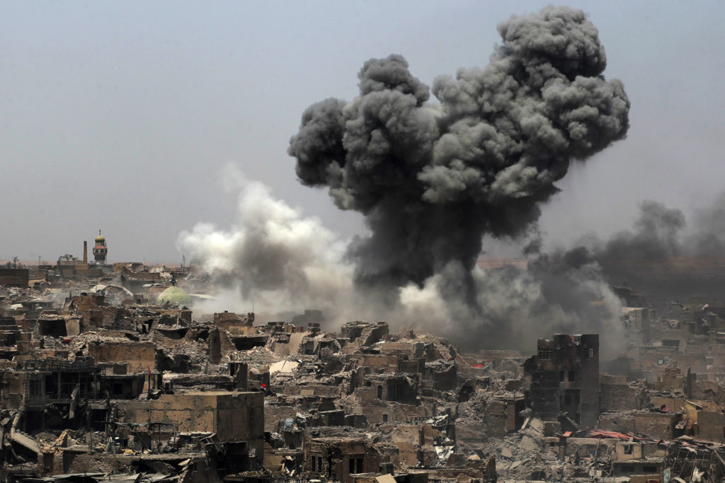 A pillar of smoke rises among destroyed buildings after a US-led airstrike in Mosul. July 9, 2017