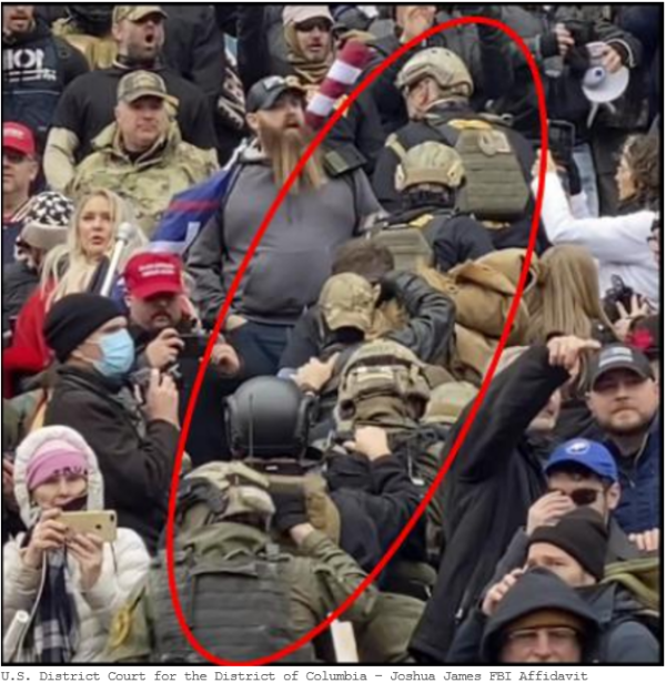 A militia walks in single file through the crowd during the January 6th attack. They wear helmets and combat gear.