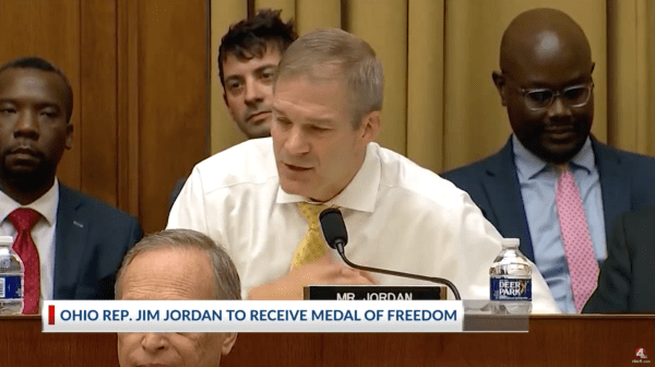 """Jim Jordan speaks into a microphone. A caption on the image reads, """"Ohio Rep. Jim Jordan to Receive Medal of Freedom"""""""
