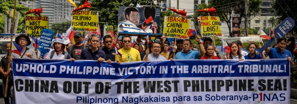 """Filipino protestors demonstrate outside the Chinese Embassy on July 12, 2019 in Makati, Metro Manila, Philippines. They carry signs reading, """"Justice for Filipino Fishermen!"""" """"Demiliterize West Philippine Sea"""" """"Uphold Philippine Victory in the Arbitral Tribunal! China Out of the West Philippine Sea!"""" and more."""