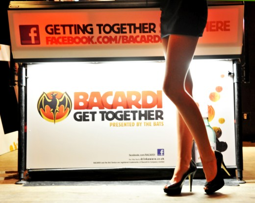 Long legs in front of a bacardi sign.