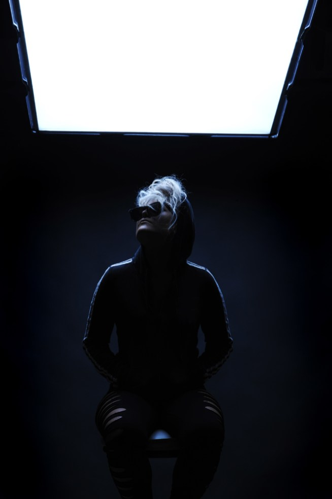 Female singer sitting being backlit with a soft box.