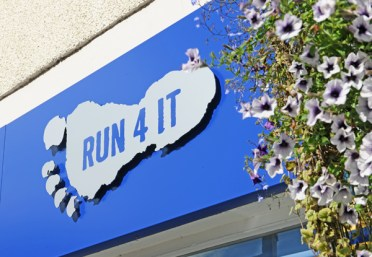 Run 4 It signage with summer flowers.