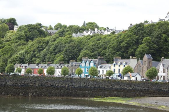 Een randje gebouwen laaggelegen rond de haven, dan een stijle heuvel waar de overige huizen bijna boven de bomen lijken te zweven.