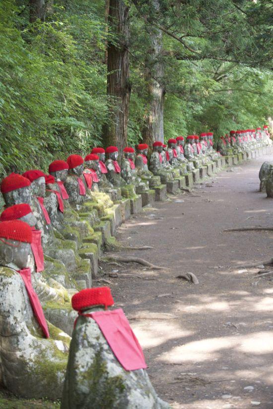 Een enorme rij Jizo beelden met rode mutsjes en slabbetjes bij Kanmangafuchi Abyss
