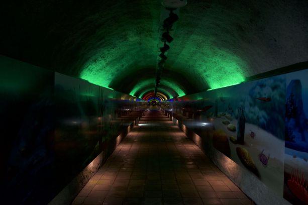 Kitsch verlichting in de tunnel naar de grot toe.