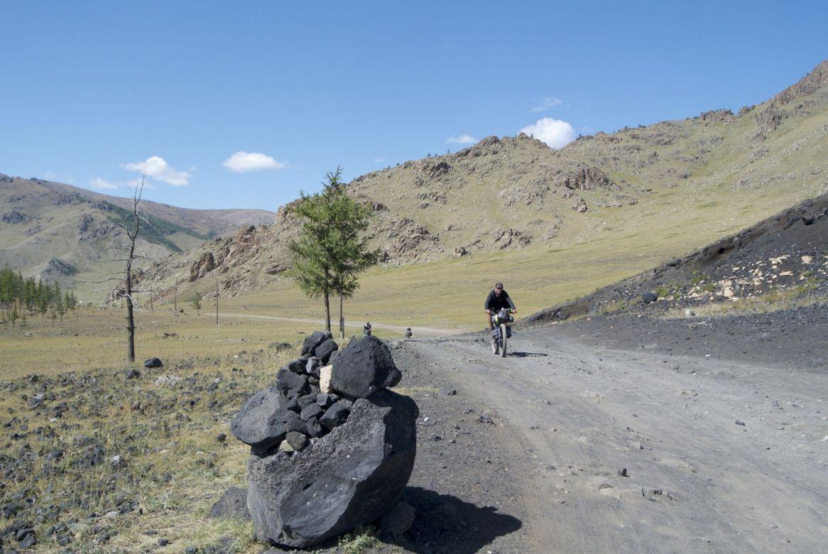 De weg kleurt hier en daar zwart met vulkanisch zand.