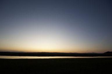 We hebben de zonsondergang helemaal voor onszelf! De hoeveelheid afval en vuurplaatsen hier naast de rivier tonen wel dat hier vaker mensen kamperen.