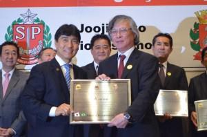 O sr. Akinori Sonoda (à dir), presidente do Kenren, recebe homenagem da Assembleia das mãos do deputado Hélio Nishimoto.