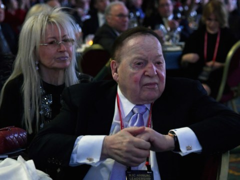 adelson and wife sit with sour looks on their faces at a gala