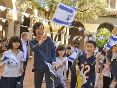 a family waves israeli flags ecstatically