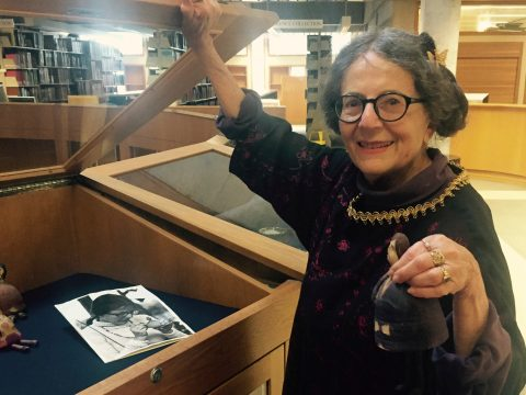 she holds open a display case and holds up one of the beatle bells for the camera to see