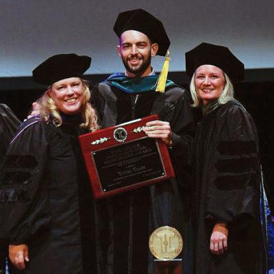 man in academic regalia holding up a plaque