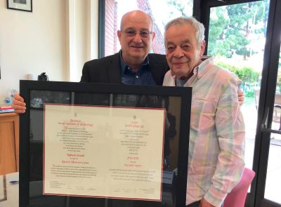 Two old men stand with a large framed degree