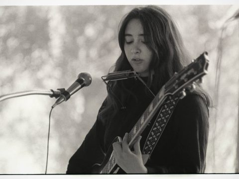 young woman with long hair playing guitar in front of a mic