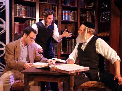 The three stand and sit around a table with volumes of Talmud arguing