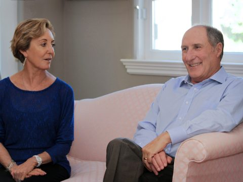 a man and a woman sit talking on a pink couch