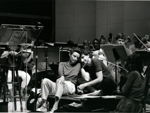 they lean on each other, sitting on his podium, surrounded by seated musicians at work