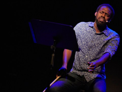 a black man in dramatic blue lighting on stage singing