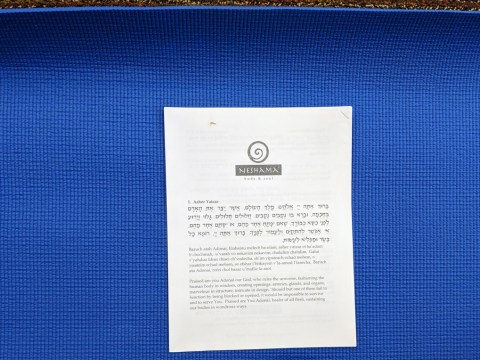 "a stapled paper packet that says ""Neshama Body & Soul"" sits on a blue yoga mat"
