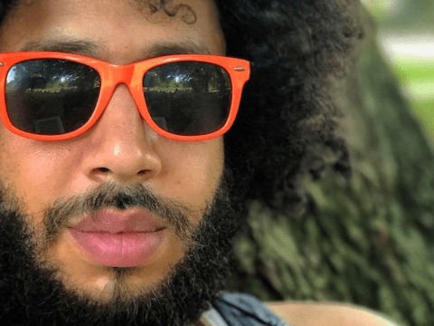 closeup of a young black man with a neat beard and orange sunglasses