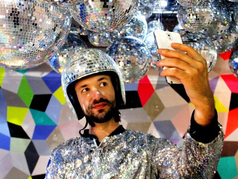a man in a glittering silver jacket with a disco ball bicycle helmet taking a selfie