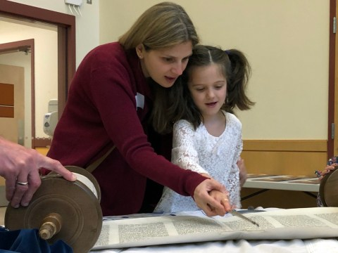 Rabbi Jill Perlman, incoming senior rabbi at Temple Isaiah in Lafayette, reading Torah with a young congregant