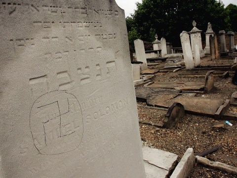 A swastika is daubed on a Jewish gravestone in London's East Ham Jewish Cemetery. (Photo/JTA-Graeme Robertson-Getty Images)