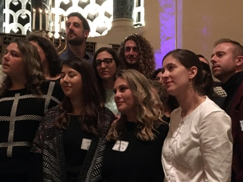 """Young adults stand to receive the priestly blessing at the """"Late Shabbat"""" 20th anniversary service at Congregation Emanu-El in S.F., Nov. 9, 2019. (Gabe Stutman)"""