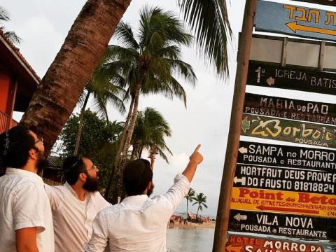 Rabbi Mendy Gerenstadt, right, points at a Chabad sign in Hebrew at a beach promenade in Morro de Sao Paulo. (Courtesy Beit Chabad)