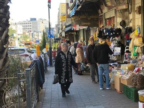 A woman walks down a busy street in Ramallah, Jan. 30. 2020. (JTA/Sam Sokol)