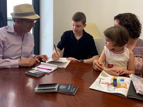 דן שיפרין ואבי פרידמן עם ילדים ליאור ואליה חותמים על מסמכי אזרחות במשרד הממשלה במלאגה, ספרד.