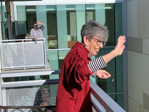 """Harriet Weiss greets neighbors during the daily """"Moldaw wave."""" Everyone at the Moldaw Residences, a Jewish retirement home in Palo Alto, is in quarantine. So every day at 5 p.m., they go out on their balconies to wave hi to each other and sing together. (FRANK WEISS)"""